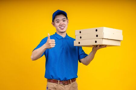 Asian delivery man holding pizza or parcel box over yellow isolate background. Work from home and delivery concept.