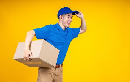 Asian delivery man holding parcel box over yellow isolate background. Work from home and delivery concept. Standard-Bild