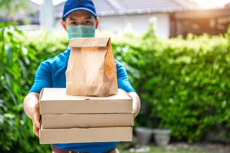 Asian deliveryman is delivering parcel to house her to sign to receive the product After she ordered online during the outbreak of the coronavirus or Covid-19 virus.