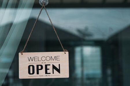 Label 'Welcome We are OPEN Welcome in' notice sign wood board hanging on door front coffee shop.
