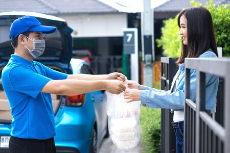 Asian delivery man delivering food, fruit, joice and vegetable to customer home - online grocery shopping service concept Standard-Bild