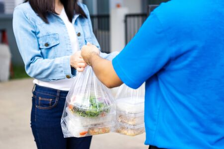 Asian delivery man delivering food, fruit, joice and vegetable to customer home - online grocery shopping service concept 版權商用圖片