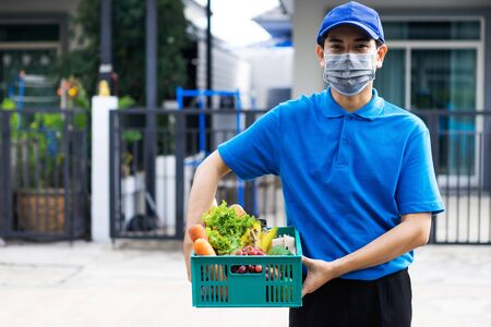 Asian delivery man blue uniform wearing medical face mask making grocery service giving fresh food to customer receiving front house, Food delivery and grocery service concept.