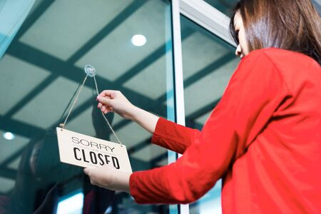 Asian woman shop owner hanging label 'Sorry we are Closed'. She close her shop under pandemic coronavirus Standard-Bild