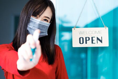 Asian woman shop owner smiling hanging label 'Welcom we are open' and showing thump up. She open her shop after pandemic of coronavirus outbreak Standard-Bild