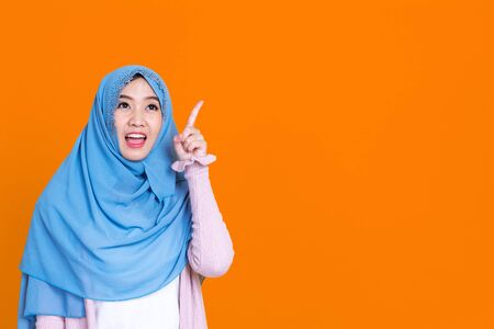 Happy Muslim woman in hijab pointing at something, isolated on color background.