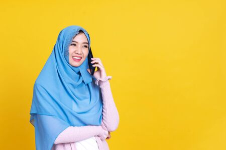 Smiling Asian muslim woman with using mobile or smartphone over isolated color background.