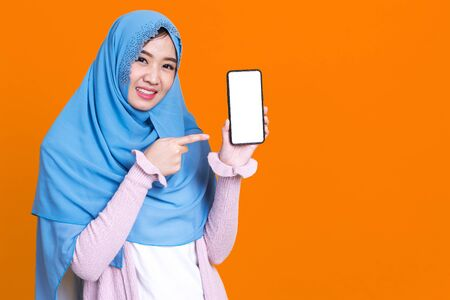 Muslim asian woman showing blank mobile phone screen over isolated color background. Foto de archivo