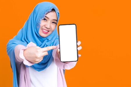 Muslim asian woman showing blank mobile phone screen over isolated color background. 写真素材