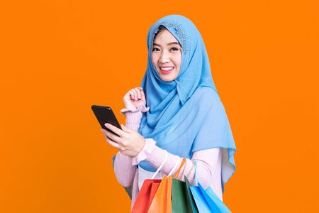 Muslim woman holding shopping bag using mobile phone and credit card isolated color background.