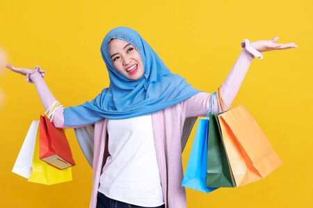 Muslim woman holding shopping bag isolated color background.