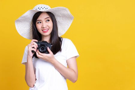 Portrait photo of Asian smiling pretty girl in white shirt taking photo on camera isolated over color background