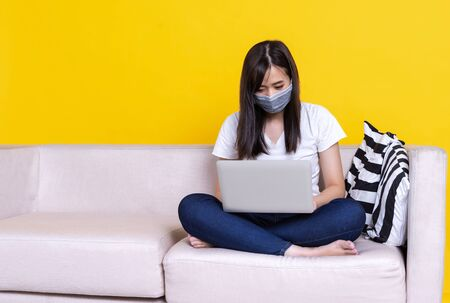 Asian woman wearing medical mask and working from home use laptop computer while sitting on sofa over isolate yellow background