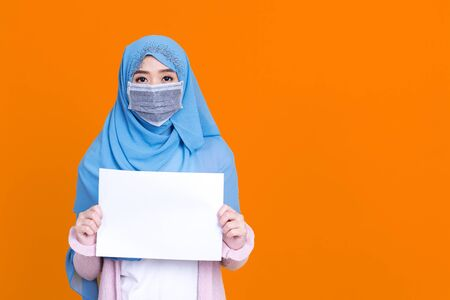 Islamic or muslim woman in hijab wearing mask protect covid-19 virus hiding behind white blank board over yellow isolated background with copy space. 写真素材