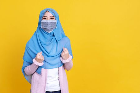 Asian muslim woman wearing hijab and medical mask over isolated background celebrating surprised and amazed for success with arms raised and open eyes. Winner concept. Foto de archivo - 149473934