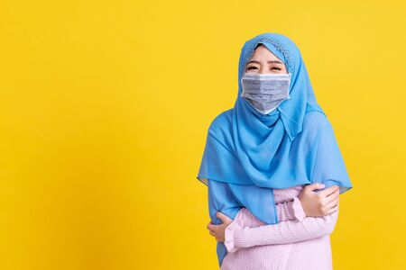 Asian muslim woman wearing muslim hijab and medical mask over isolated background shaking and freezing for winter cold with sad and shock expression on face