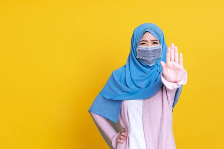 Asian serious muslim woman wears hijab, makes cross with hands over chest, shows stop or prohibition gesture, disagrees with uninteresting offer, isolated over blue background. No sign