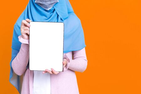 Islamic or muslim woman in hijab wearing mask protect covid-19 virus hiding behind white blank tablet screen over yellow isolated background with copy space.