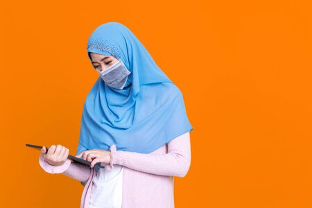 Asian Muslim woman wearing medical mask in hijab and using digital tablet isolated on color background