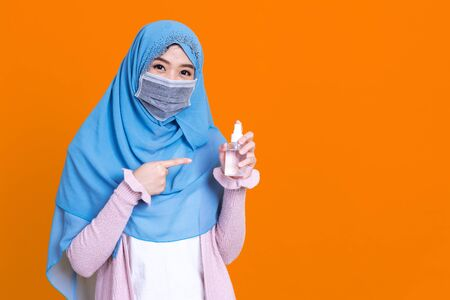 Muslim asian woman with traditional dress wearing medical face mask under the outbreak of the virus,Wash her hands with an alcohol gel isolated on color background 写真素材