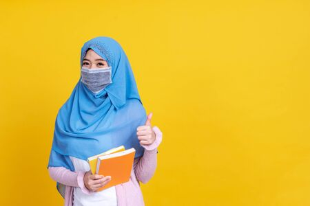 Asian muslim woman in hijab and wearing medical mask and holding book over isolate color background. Education concept.