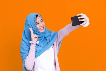 Happy Asian muslim woman taking selfie with smartphone isolated on color background