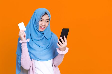 Asian muslim woman hijap happy using mobile phone to shopping with credit card over color background 写真素材