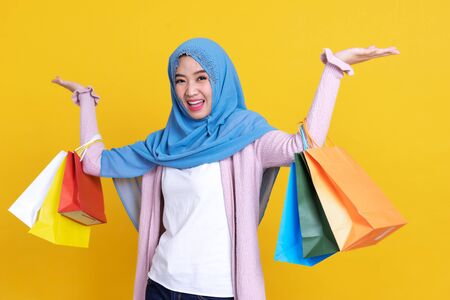 Asian muslim woman hijap happy with shopping bag using credit card to shopping over color background 写真素材