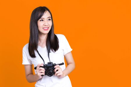 Asian woman smiling pretty girl in white shirt taking photo on camera isolated over color background