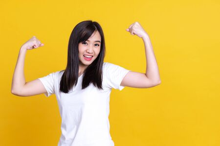 Asian gorgeous strong young pin-up woman smiling isolated over background wall showing biceps screaming. 写真素材