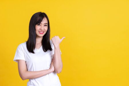 Beauty smiling brunette Asian woman pointing away and smiling and looking at the camera over yellow background Standard-Bild
