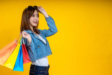 Portrait of Asian woman nice attractive wearing sun glasses carrying new shopping bag showing a credit card on bright isolated yellow color background. Shopping concept. 写真素材