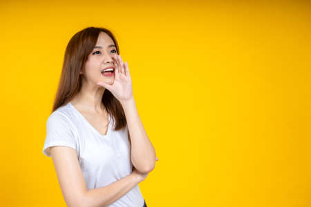 Young Asian woman in white casual t-shirt looking aside, shouting or annoucing something over yellow wall background in studio. People lifestyle concept. Mock up copy space