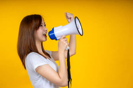 Young Asian woman in white casual t-shirt looking aside, scream in megaphone isolated on bright yellow wall background in studio. People lifestyle concept. Mock up copy space 写真素材