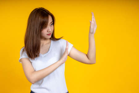 Asian woman making stop gesture isolated on yellow background with copy space 写真素材