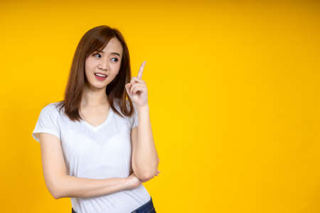 Young elegant Asian woman smiling and pointing to empty copy space isolated on yellow background 写真素材