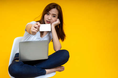 Young Asian woman smiling sitting crossed legs on chair with laptop computer holding credit card for shopping online on isolated yellow background. Work from home and shopping online concept. 写真素材