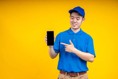 Asian delivery man pointer to application on mobile phone over yellow isolate background. Work from home and delivery concept. 写真素材