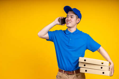 Asian delivery man using mobile phone call to customer over yellow isolate background. Work from home and delivery concept.