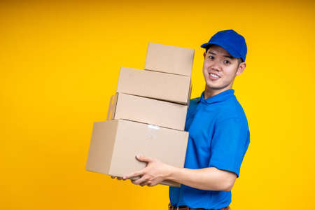 Asian delivery man holding parcel box over yellow isolate background. Work from home and delivery concept. 写真素材