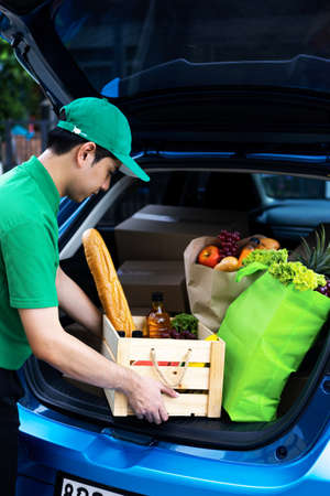 Asian delivery man in green t-shirt delivering food, fruit, joice and vegetable to home - online grocery shopping service concept