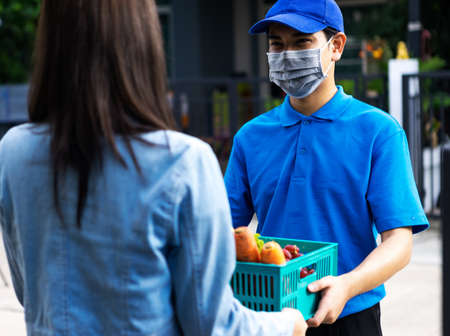 Asian delivery man delivering food, fruit, joice and vegetable to customer home - online grocery shopping service concept 写真素材