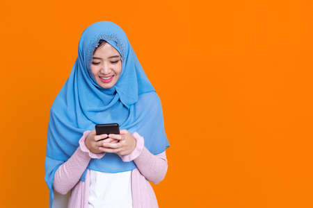Smiling Asian muslim woman with using mobile or smartphone exciting over isolated color background.