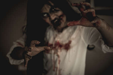 Woman in ghost or zombie on halloween festival at dark place, holding knife and wants to stab you. Horror or halloween festival concept.