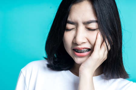 Teenage woman wearing braces and she is having a toothache isolate background Standard-Bild