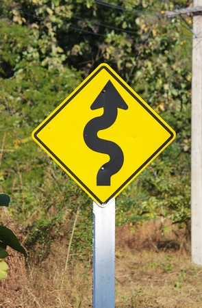 Curvy road sign on a country road photo