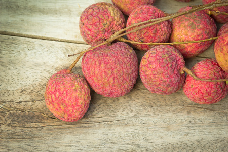 lychees: fresh lychees on wooden background