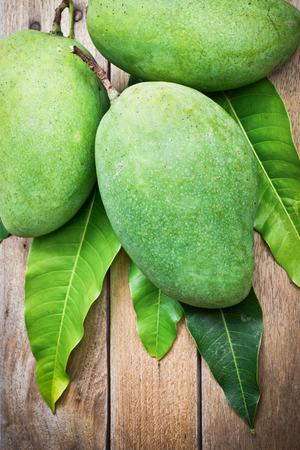 green mango: Fresh green mango on wooden table, Tropical fruit