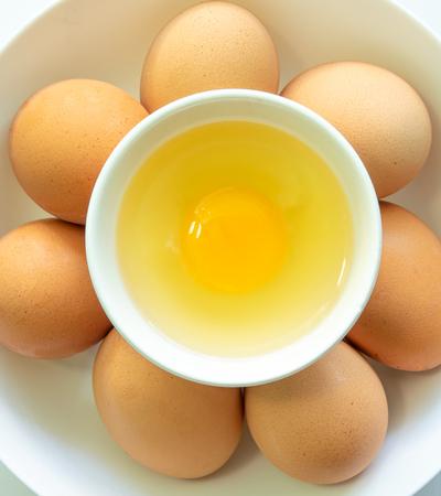 Top view of fresh eggs in bowl, closeup