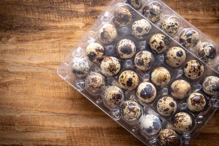 Quail eggs in  packaging on wooden background and space for text